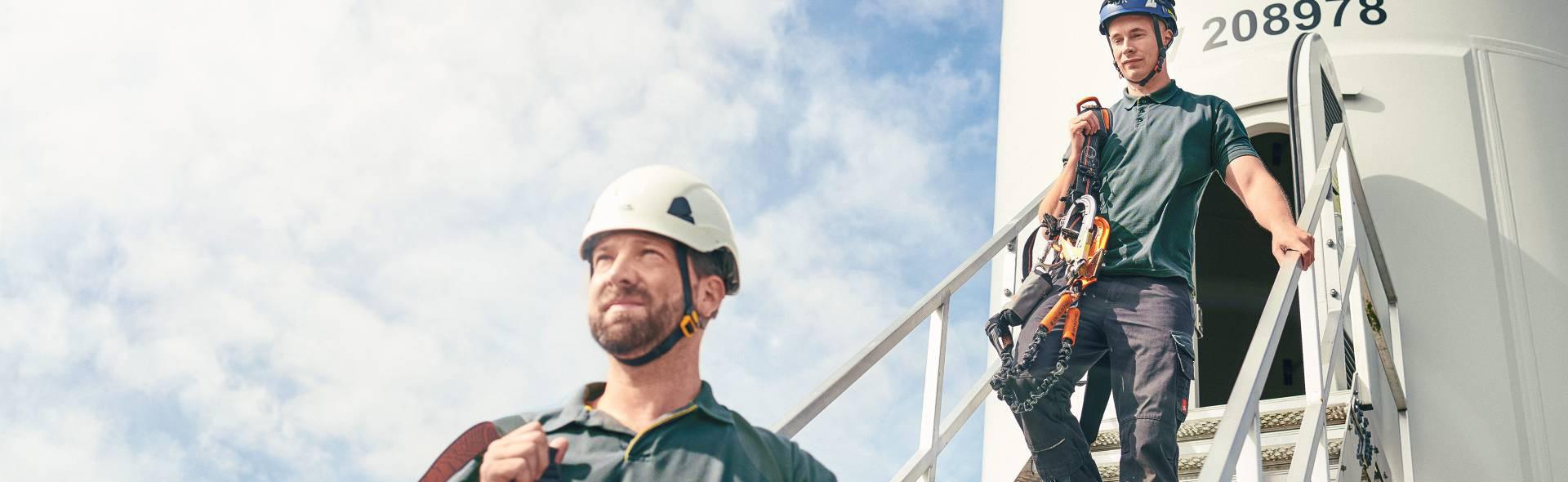 Zwei Techniker verlassen ein Windrad nach der Wartung